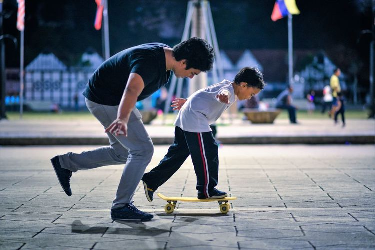 Side view of coach teaching student balancing on skateboard at park