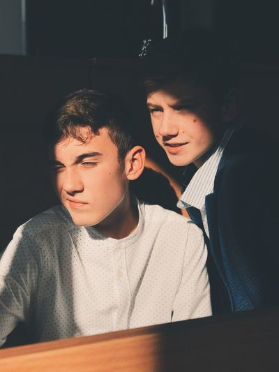 Close-up of young men looking away by wooden table