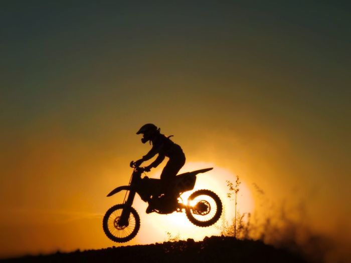 Silhouette man riding motorcycle against orange sky