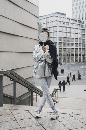 Young woman holding mirror while standing on steps in city