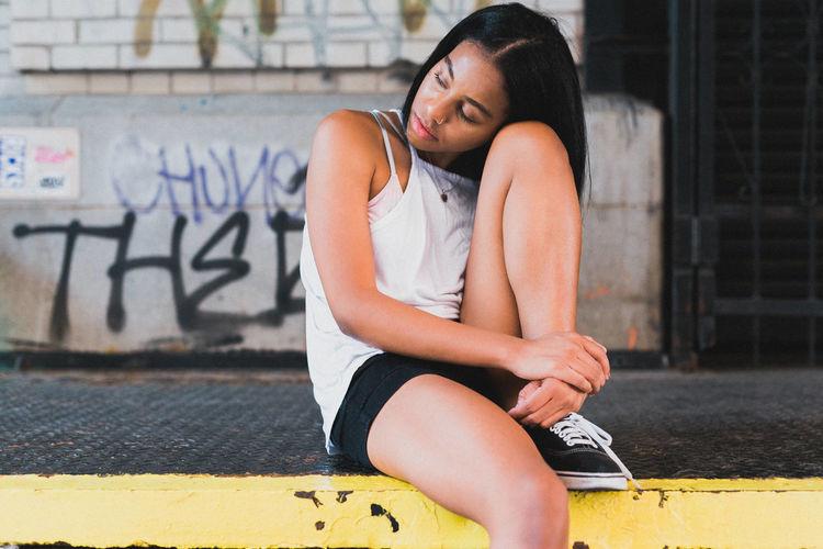 Young Woman Sitting On Sidewalk