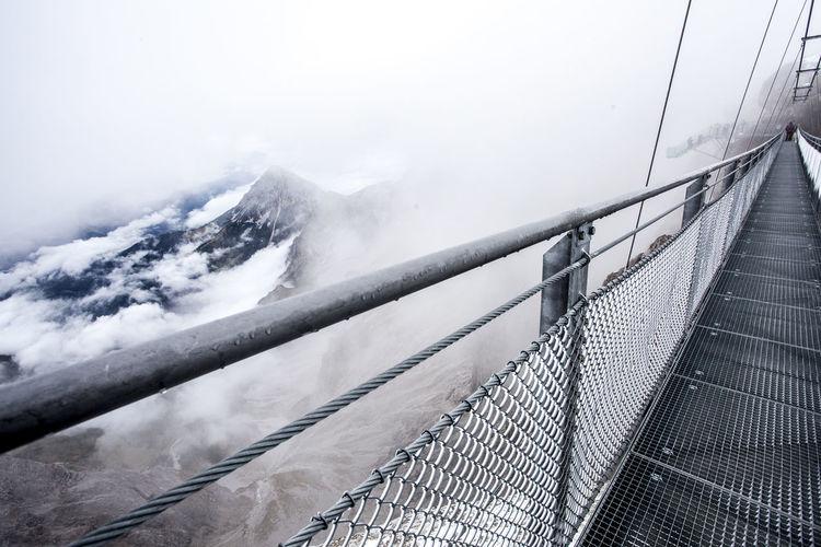 Narrow footbridge along snowed mountains