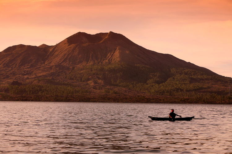 Man In Boat On Lake Against Mount Batur