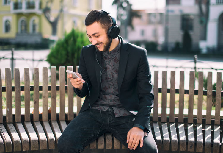 One Person Young Adult Communication Front View Three Quarter Length Architecture Young Men Mobile Phone Technology Sitting Wireless Technology Real People Casual Clothing Focus On Foreground Smart Phone Connection Lifestyles Looking Railing Outdoors Contemplation
