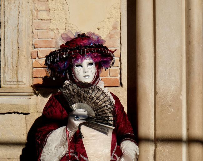 Portrait of mature woman wearing costume while holding hand fan during venice carnival