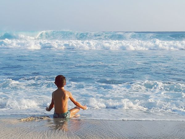 Kid Meditation Beach Sea Wave Vacations Summer One Person People Shirtless Full Length Surfing Horizon Over Water Water Sunlight Children Only Leisure Activity One Boy Only Outdoors Boys Sky Day Travel Destinations Tranquility Meditation Scene Meditation Natural Mediation