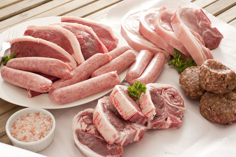 Raw pork and sausages with seasoning on white plates and wax paper ready for cooking outdoors Fat Food Food And Drink Fresh Meat Outdoors Paper Pork Protein Raw Red Sausages Selection Slices Steak Table Uncooked