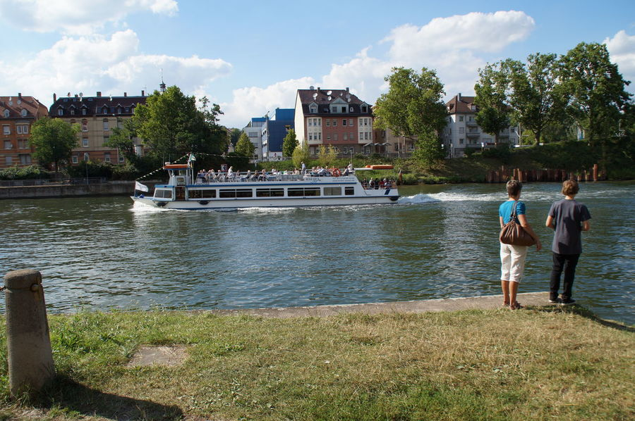 Overlooking the Neckar in Bad Cannstatt. A tourist ship sails straight to the city side by, a woman and a teenager standing on the untouched natural side of the river and watch the river. Bad Cannstatt Bulidings Enyoing The Moment Mother Neckar Shiny Ship Stuttgart Tourism Tourism Destination
