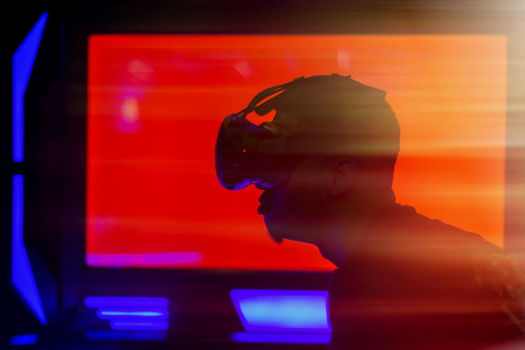 Virtual Reality Simulator Young Adult Vr Silhouette Side View Illuminated Device Screen Communication One Person Indoors  Headshot Portrait Red Technology Real People Looking Men Close-up Lifestyles Adult Arts Culture And Entertainment Contemplation Digital Composite Profile View