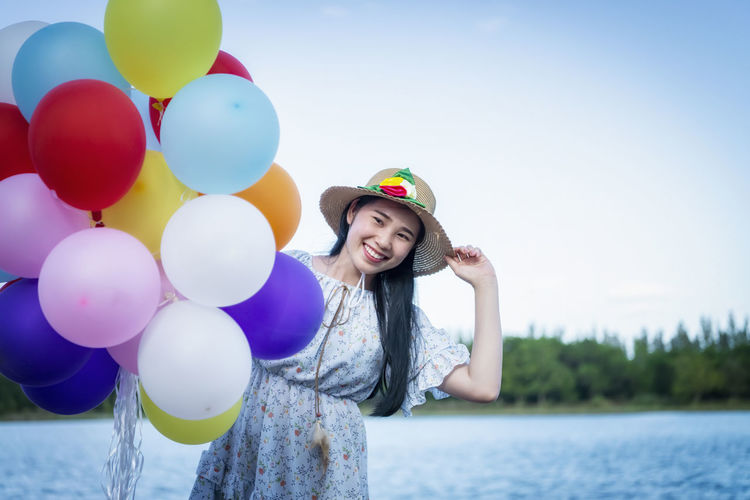 Portrait of smiling young woman standing at balloons against sky