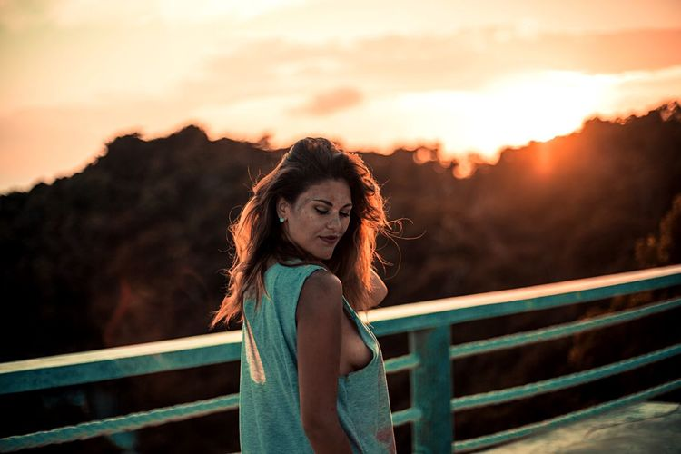 Young woman standing on footbridge against sky during sunset