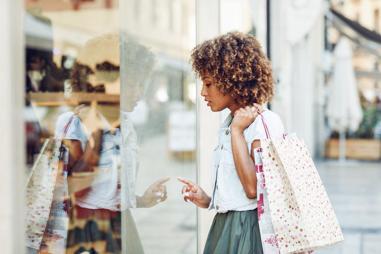 Woman holding shopping bags while looking at store