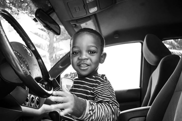 Portrait of smiling boy in car