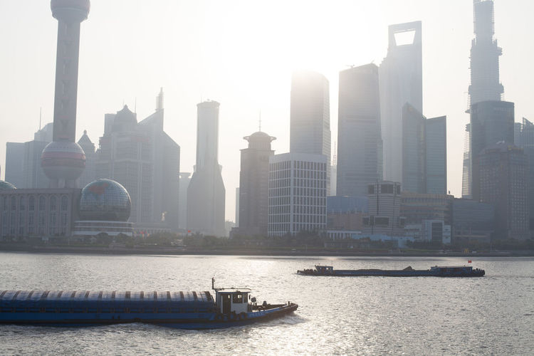 Oriental Pearl Tower And Financial District By River On Sunny Day
