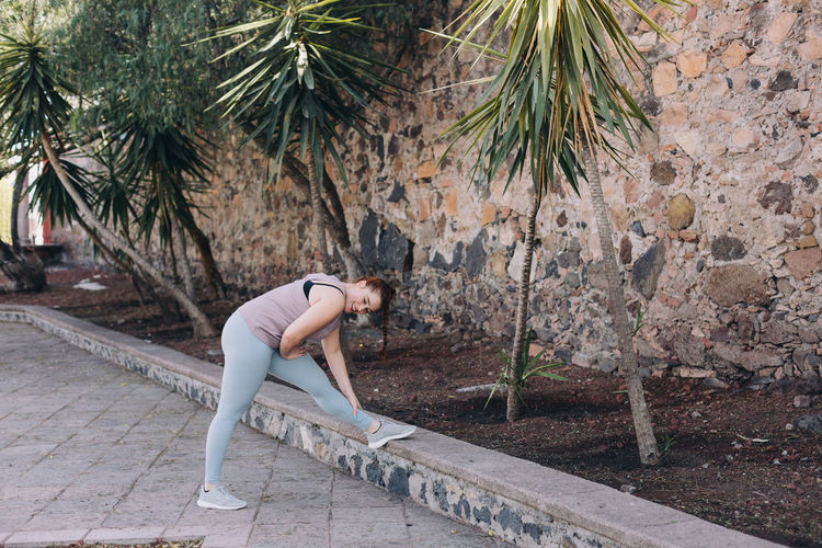 Side view of woman stretching against trees