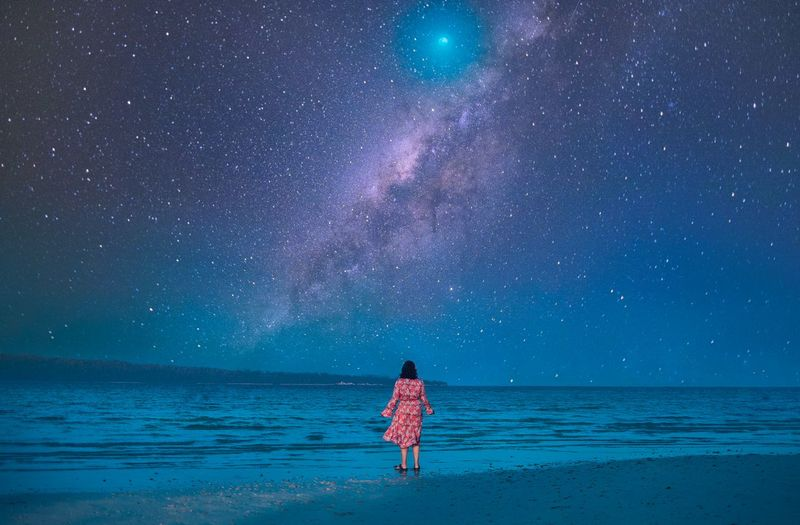 Rear view of man standing at beach against sky at night