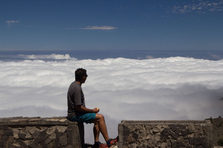 Man sitting on mountain watching the sea of clouds below him