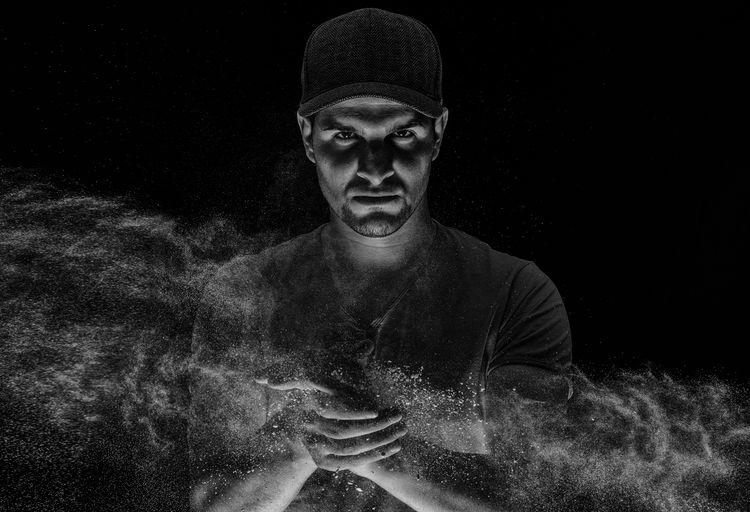 Portrait of man using chalk against black background