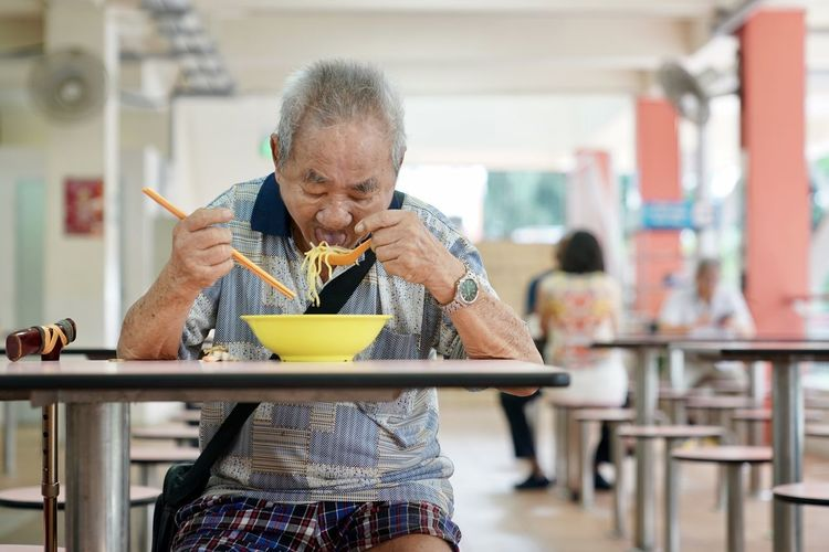 Eating Noodles Adult Breakfast Casual Clothing Chop Sticks Eating Utensil Focus On Foreground Food Food And Drink Front View Holding Indoors  Kitchen Utensil Lifestyles Men One Person Real People Senior Adult Sitting Spoon Table Waist Up The Photojournalist - 2018 EyeEm Awards The Traveler - 2018 EyeEm Awards The Portraitist - 2018 EyeEm Awards The Street Photographer - 2018 EyeEm Awards