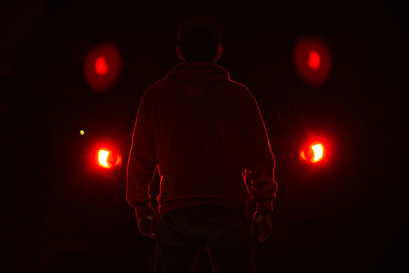 Rear view of man standing against illuminated lights at night