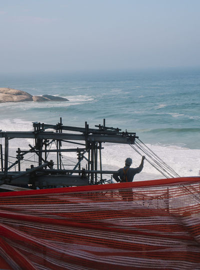 People working on bridge over sea against sky