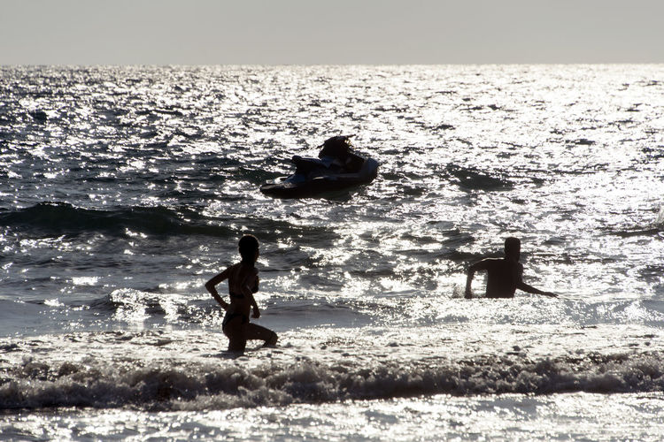 SILHOUETTE OF People playing, swimming in the waves in the island of Patmos, Greece in summer time Beach Beauty In Nature Day Horizon Horizon Over Water Land Leisure Activity Lifestyles Men Motion Nature Outdoors People Real People Sea Silhouette Sky Two People Water Wave
