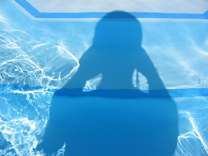 Shadow of person on swimming pool