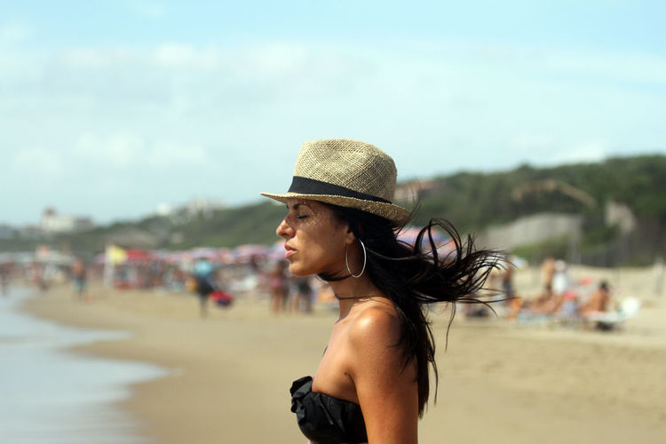 Side view of woman with eyes closed wearing hat standing at beach