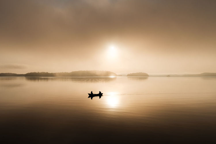 Silhouette man on boat in lake against sky during sunset