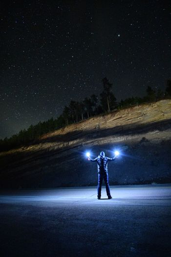 Man standing by illuminated light against sky at night