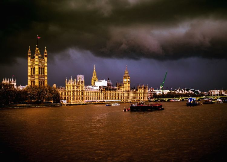 Boats Moving On Thames River By Big Ben Against Cloudy Sky