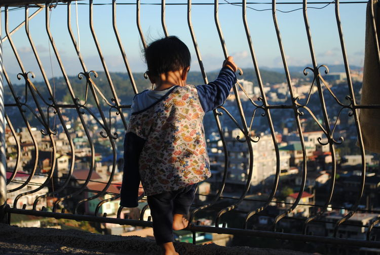 Rear view of child standing by railing