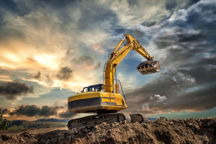 Earth mover at construction site against sky during sunset