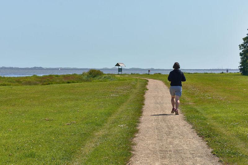 Rear view of man walking on field against clear sky