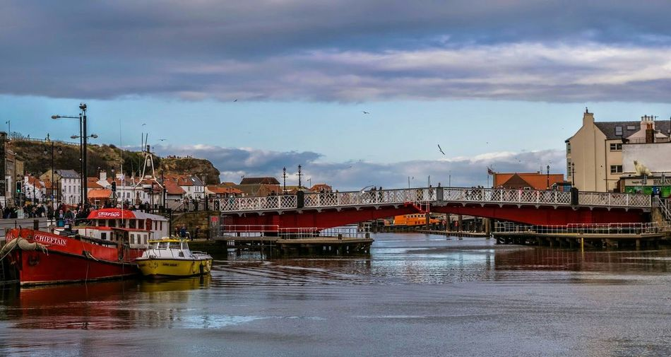 Boats Moored In River Near Bridge Against Cloudy Sky