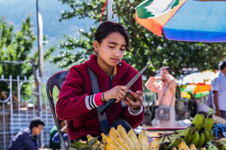 Asian  Himalayas Adult Bhutan Business Casual Clothing Day Focus On Foreground Girl Hair Holding Lifestyles Looking Market Outdoors People Portrait Real People Sitting Table Women Young Adult