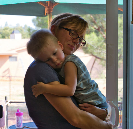 Smiling Mother Carrying Cute Son While Standing By Door