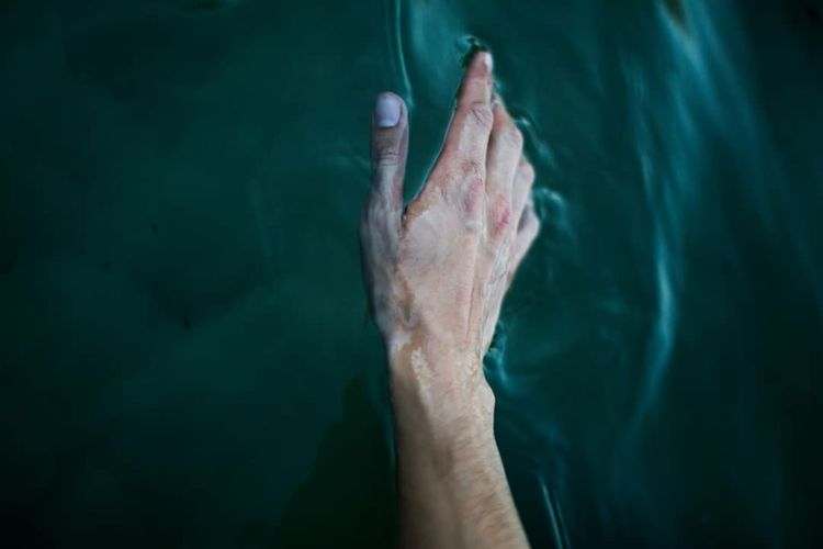 Close-up of hand against sea