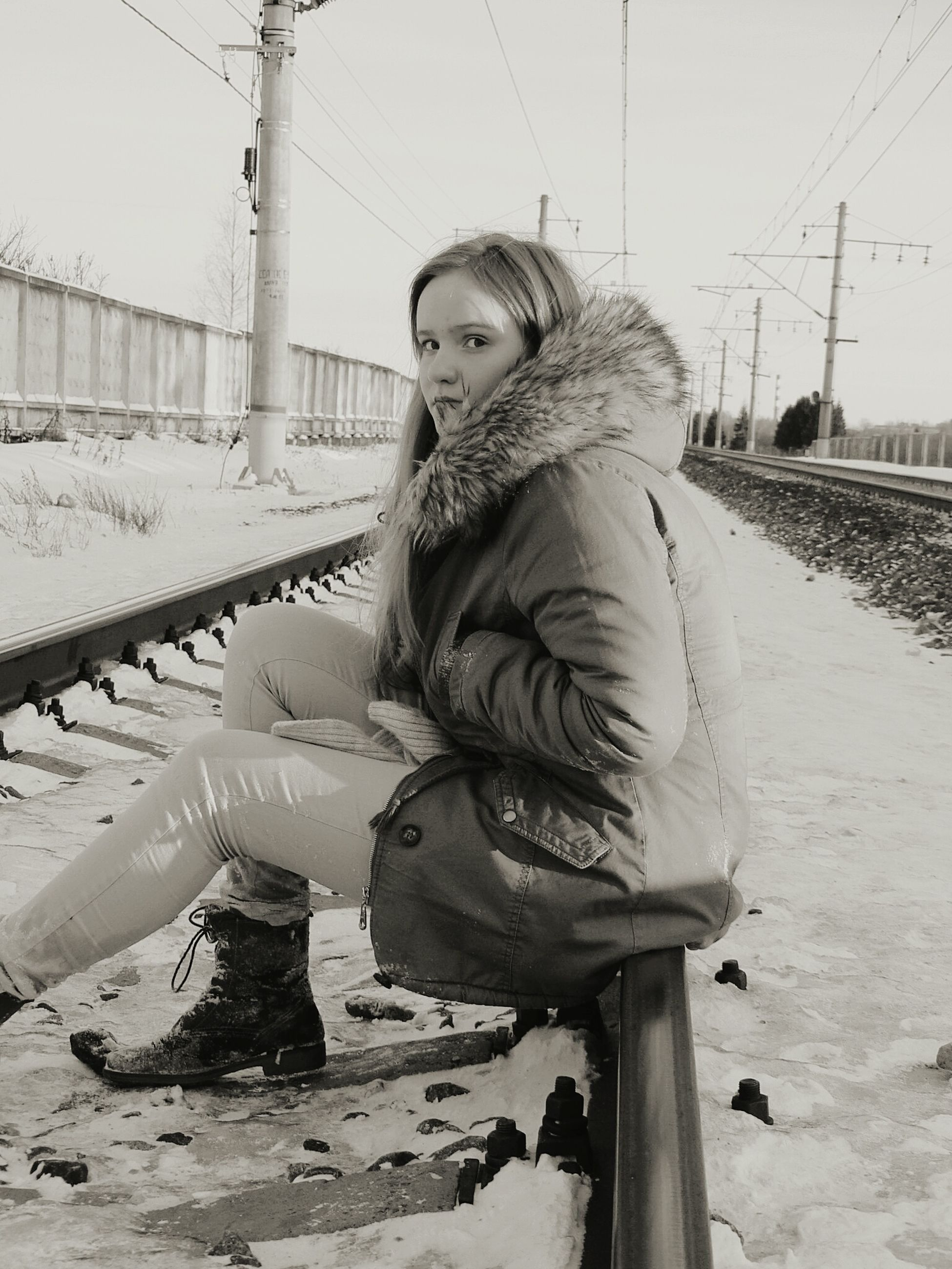 snow, winter, cold temperature, lifestyles, full length, season, casual clothing, transportation, warm clothing, person, leisure activity, standing, young adult, looking at camera, front view, weather, road, railroad track