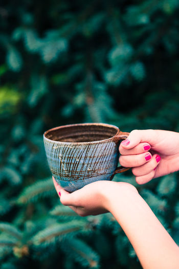 Female hand holding earthen cup with herbal tea with green natural background