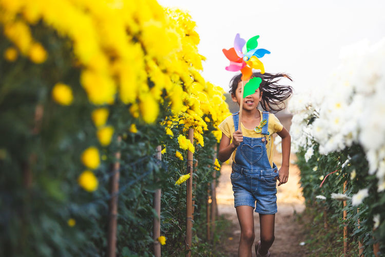Girl running with pinwheel toy amidst flowering plants