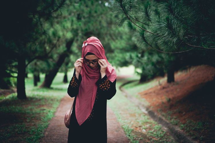 Young woman in hijab standing against trees in forest