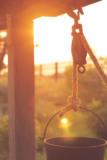 Close-up of chain hanging on rope against sunset