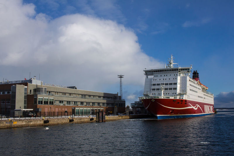 Ship moored at harbor against sky