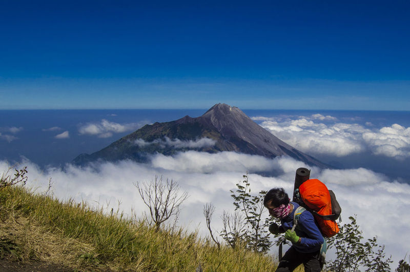 High angle view of man hiking on mountain against sky