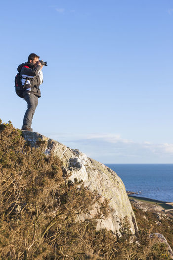 Photogragpher backpacker at the cliff Sea Sky Water Rock - Object Standing Leisure Activity One Person Scenics - Nature Real People Lifestyles Rock Solid Beauty In Nature Horizon Photography Themes Activity Nature Horizon Over Water Photographing Outdoors Photographer