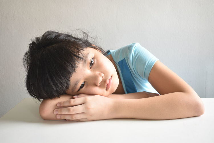 Close-up of girl lying down on table against wall