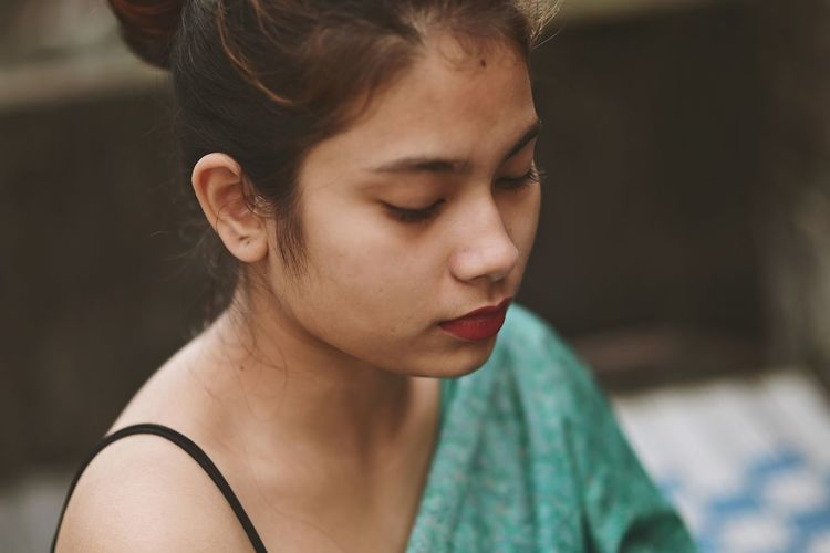 Close-up portrait of a young woman looking away
