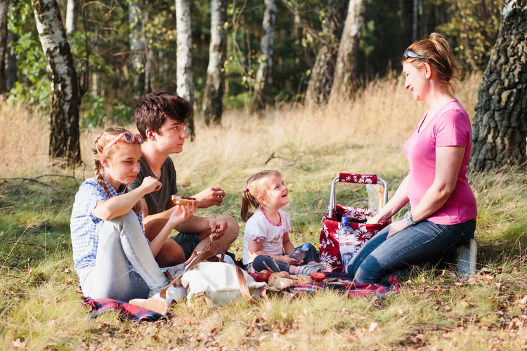 Family spending vacation time together having a snacks on a picnic sitting on blanket on grass in forest on sunny day in the summertime Children Family Moments Mother Picnic Recreation  Relaxing Summertime Vacation Time Vacations Child Childhood Family Time Forest Joy Joy Of Life Leisure Leisure Activity Outdoors People Recreational Pursuit Relaxing Time Summer Summer Vibes Togetherness