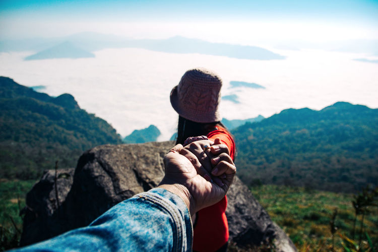 Woman holding hand of man on mountain